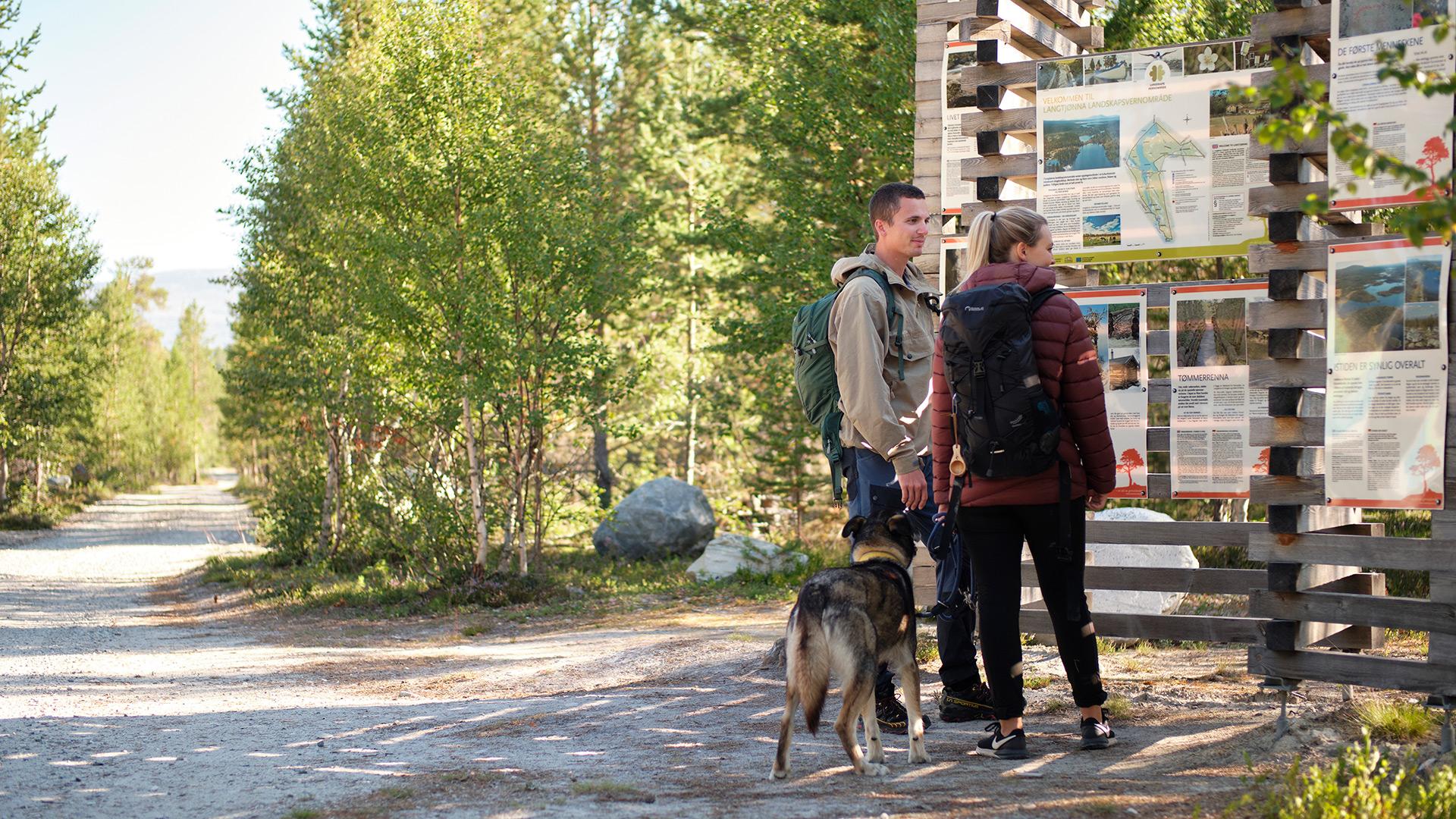Personer og en hund ser på informasjonstavle.